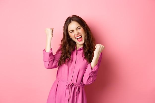Piękna uśmiechnięta kobieta krzyczy z radosną i podekscytowaną twarzą, mówi tak, pompuje pięścią, wygrywa i czuje się jak mistrz, triumfująca, stojąca nad różową ścianą.