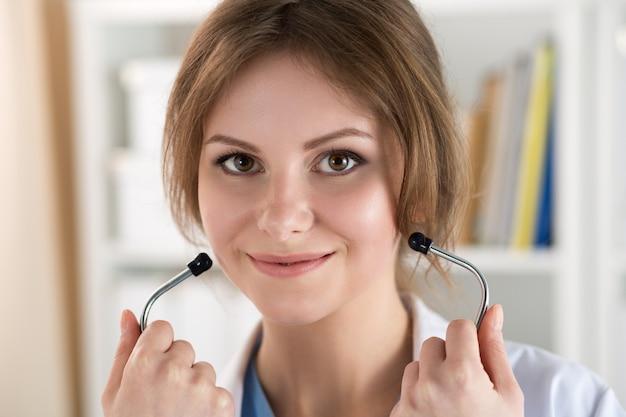 Piękna uśmiechnięta kobieta lekarz medycyny trzyma i stawia na zbliżenie stetoskop. zdrowe serce i styl życia, lekarz gotowy do zbadania koncepcji profilaktyki pacjenta, opieki zdrowotnej, fizycznej i choroby