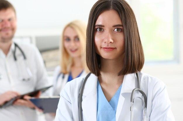Piękna uśmiechnięta kobieta lekarz stoi w portrecie biurowym
