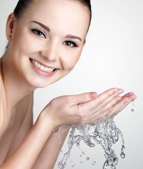 Piękna uśmiechnięta kobieta myje twarz wodą