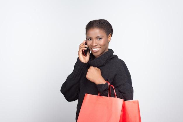 Piękna uśmiechnięta kobieta opowiada na telefonie
