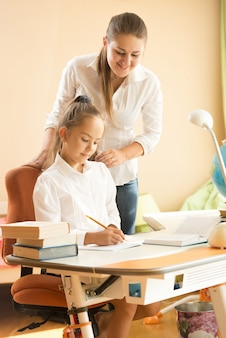 Piękna uśmiechnięta kobieta patrząca na dziewczynę odrabiającą pracę domową w sypialni