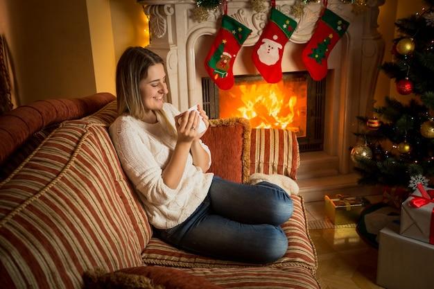 Piękna uśmiechnięta kobieta pijąca herbatę przy płonącym kominku w boże narodzenie