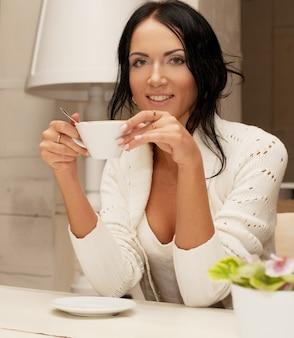 Piękna uśmiechnięta kobieta pije kawę. dom.