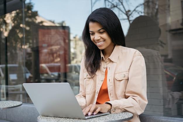 Piękna uśmiechnięta kobieta pracująca online, przy użyciu komputera przenośnego, pisania, oglądania kursów szkoleniowych na stronie internetowej