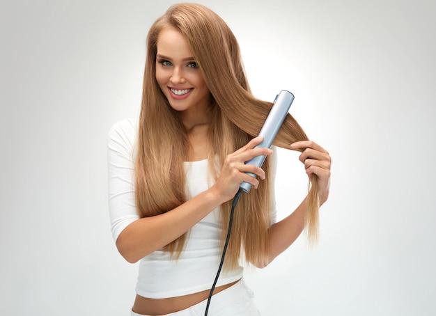 Piękna uśmiechnięta kobieta prostowania zdrowych długich blond włosów