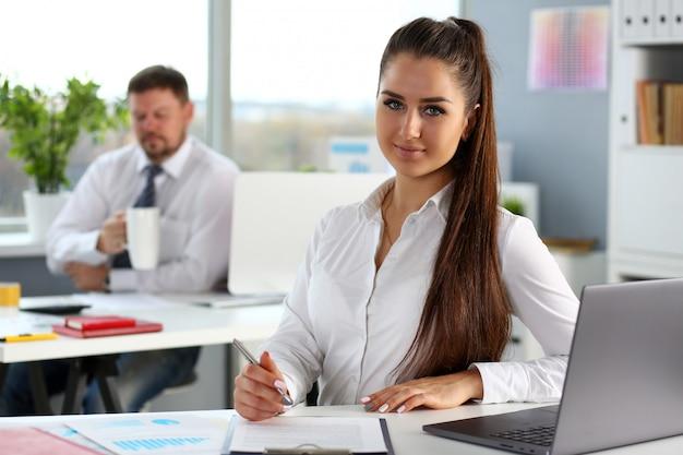 Piękna uśmiechnięta kobieta przy miejscem pracy