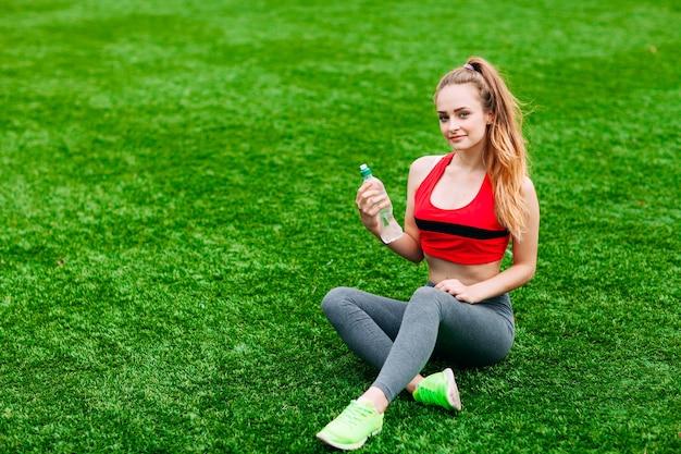 Piękna uśmiechnięta kobieta relaks na trawie w parku podczas treningu. koncepcja sportu i fitness