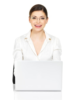Piękna uśmiechnięta kobieta siedzi od stołu thñƒ z laptopem w białej koszuli - na białym tle.