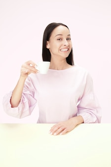 Piękna uśmiechnięta kobieta siedzi w różowym studio i patrząc szczęśliwy, trzymając w ręku filiżankę kawy. zbliżenie stonowanych portret w stylu minimalizmu
