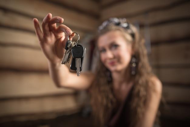 Piękna uśmiechnięta kobieta trzyma rozmyte klucze w dłoniach. kredyt hipoteczny i nowa koncepcja mieszkaniowa. dziewczyna trzyma kluczyki do samochodu. koncepcja zakupu domu