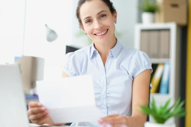 Piękna uśmiechnięta kobieta trzymająca w rękach list z dokumentem zadowolona z powiadomienia o zatwierdzeniu kredytu
