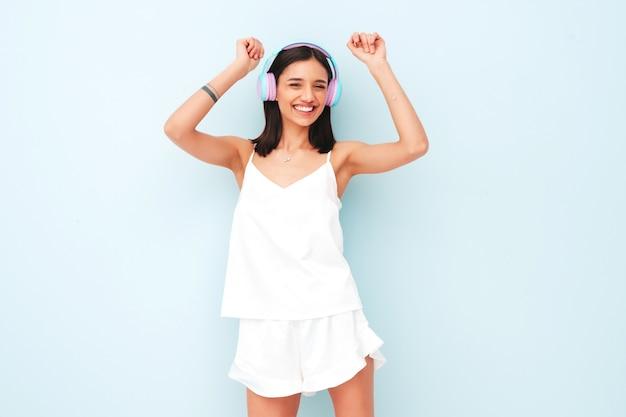 Piękna uśmiechnięta kobieta ubrana w białą piżamę