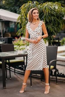 Piękna uśmiechnięta kobieta ubrana w białą sukienkę z nadrukiem w romantycznym stylu pozuje w ulicznej kawiarni w słoneczny dzień