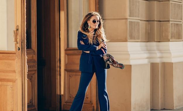 Piękna uśmiechnięta kobieta ubrana w elegancki garnitur i okulary przeciwsłoneczne spacerująca ulica uśmiechnięta przy słonecznej pogodzie