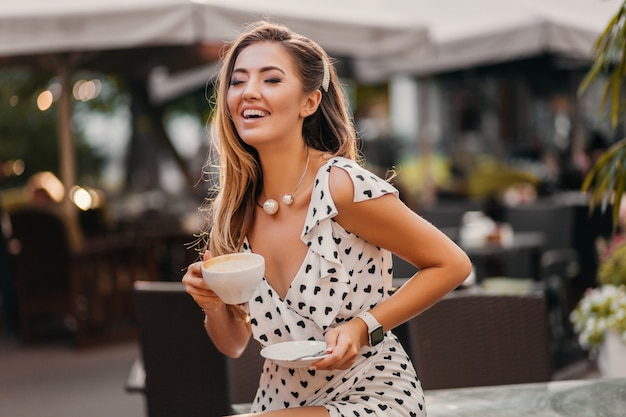 Piękna uśmiechnięta kobieta ubrana w stylową białą drukowaną sukienkę siedzi w kawiarni ulicy z filiżanką cappuccino