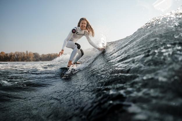 Piękna uśmiechnięta kobieta w białym stroju kąpielowym jeżdżąca na wakeboardzie na zginanych kolanach