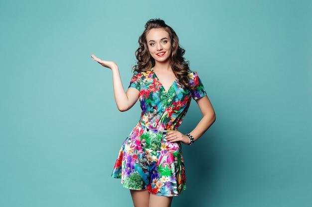Piękna uśmiechnięta kobieta w kwiecistej sukni z ręką na talii demonstruje coś na tle.