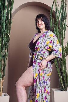 Piękna uśmiechnięta kobieta w lekkiej jedwabnej tuniki na plażę