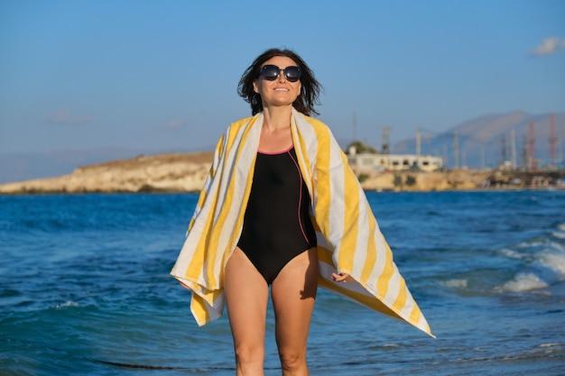 Piękna uśmiechnięta kobieta w średnim wieku spaceru wzdłuż plaży w słoneczny letni dzień