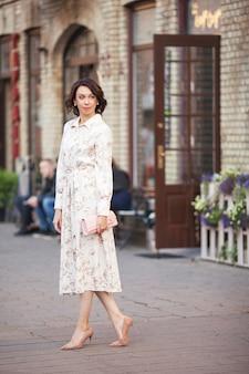 Piękna uśmiechnięta kobieta w średnim wieku w sukience spaceru ulicą miasta w słoneczny dzień.