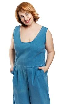 Piękna uśmiechnięta kobieta w średnim wieku z rudymi włosami w dżinsowych kombinezonach