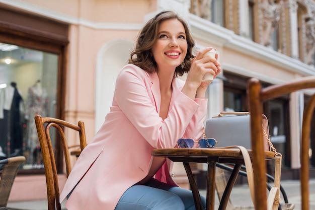 Piękna uśmiechnięta kobieta w stylowym stroju siedzi przy stole w różowej kurtce, romantyczny szczęśliwy nastrój, czeka na chłopaka na randkę w kawiarni, trend w modzie wiosna-lato, picie kawy