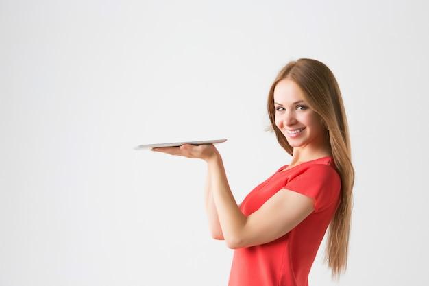 Piękna uśmiechnięta kobieta z elektronicznym tabletem na białym tle