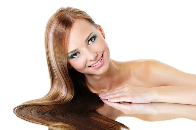 Piękna uśmiechnięta kobieta z prostymi błyszczącymi włosami