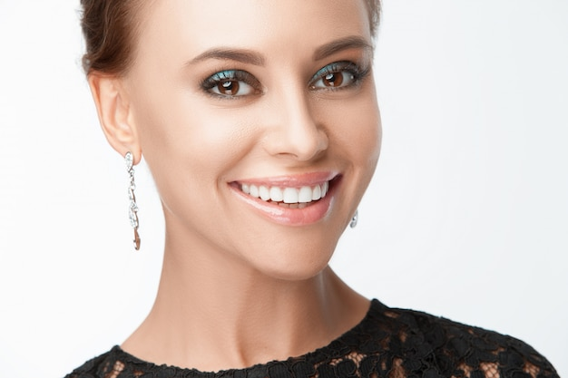 Piękna uśmiechnięta kobieta z wieczór makijażem. biżuteria i piękno. fotografia mody