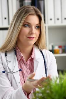 Piękna uśmiechnięta lekarka siedzi w miejscu pracy