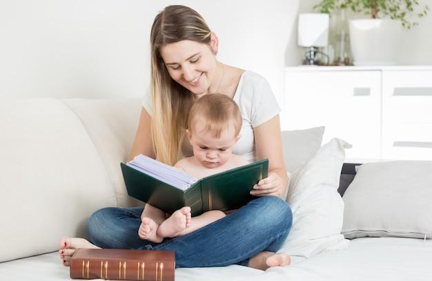 Piękna uśmiechnięta matka czytająca historię swojemu 9 miesięcznemu chłopcu