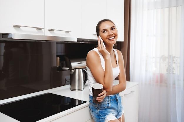 Piękna uśmiechnięta młoda dziewczyna opowiada na telefonie przy kuchnią i pije kawę