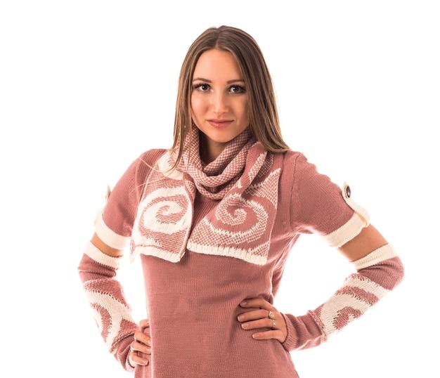 Piękna uśmiechnięta młoda dziewczyna pozuje w studio w stylowej sukience z dzianiny z szalikiem i rękawami. koncepcja stylowych ubrań kobiet.