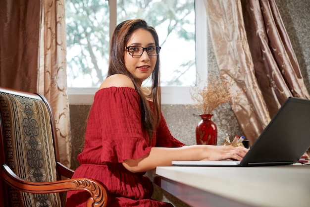 Piękna, uśmiechnięta młoda indyjska bizneswoman pracująca w domu z powodu pandemii koronawirusa