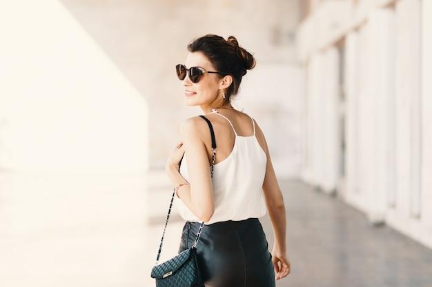 Piękna uśmiechnięta młoda kobieta patrzeje daleko od nad th w okularach przeciwsłonecznych