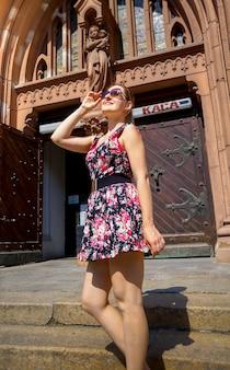 Piękna uśmiechnięta młoda kobieta pozuje na starych kamiennych schodach przed katolicką katedrą na starym mieście