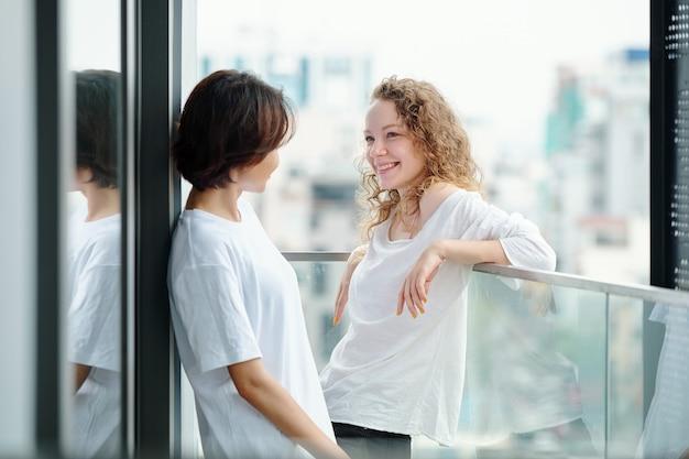 Piękna uśmiechnięta młoda kobieta stojąc na balkonie i patrząc na swoją dziewczynę