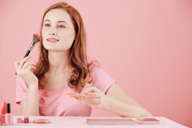 Piękna, uśmiechnięta młoda kobieta, stosując prasowany rumieniec, siedząc przy próżności i robiąc makijaż
