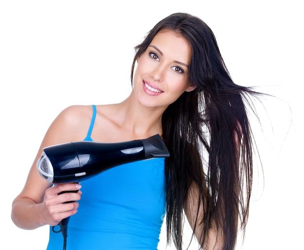 Piękna uśmiechnięta młoda kobieta suszy włosy suszarką do włosów - na białym tle