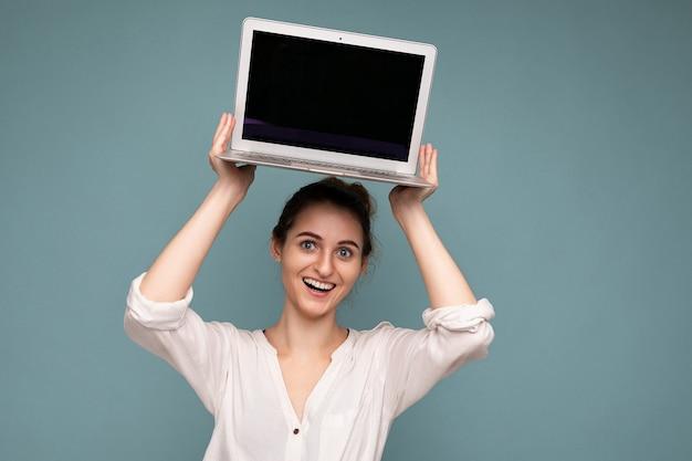 Piękna uśmiechnięta młoda kobieta trzyma komputer netbook, patrząc na kamerę, ubrana w białą koszulę na białym tle na niebieskim tle