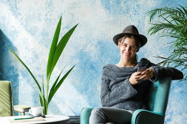 Piękna uśmiechnięta młoda kobieta ubrana w sweter i kapelusz siedzi na krześle przy stoliku kawiarnianym, trzymając telefon komórkowy, stylowe wnętrze
