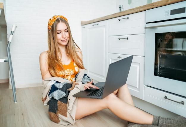 Piękna uśmiechnięta młoda kobieta uczciwe długie włosy dziewczyna ubrana w przytulny sweter z dzianiny pracujący na laptopie w jasnej kuchni, randki online