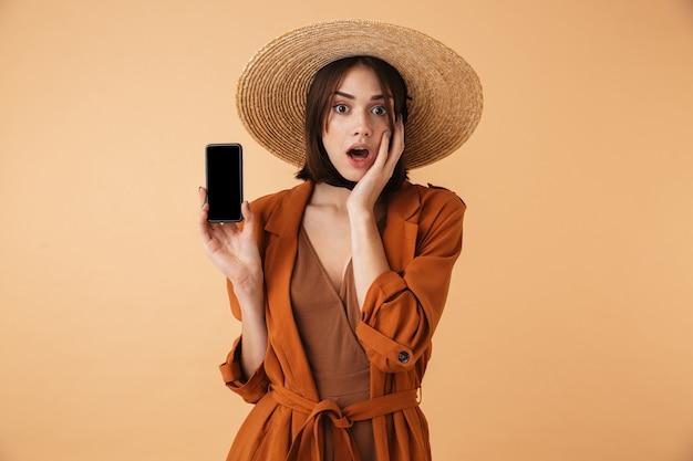 Piękna uśmiechnięta młoda kobieta w słomkowym kapeluszu stojąca na białym tle nad beżową ścianą, pokazująca pusty ekran telefonu komórkowego