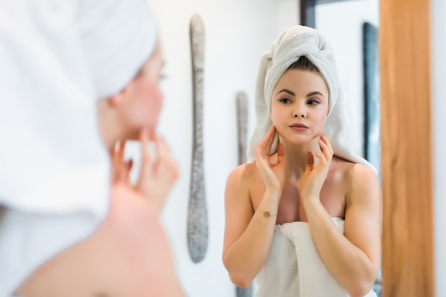 Piękna uśmiechnięta młoda kobieta w szlafroku i ręczniku dotykając twarzy, patrząc w lustro w łazience