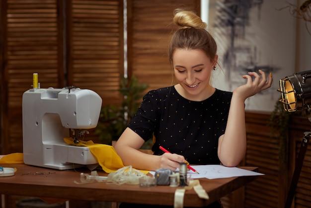 Piękna uśmiechnięta młoda krawcowa pracuje na maszynie do szycia. miejsce pracy krawcowej.