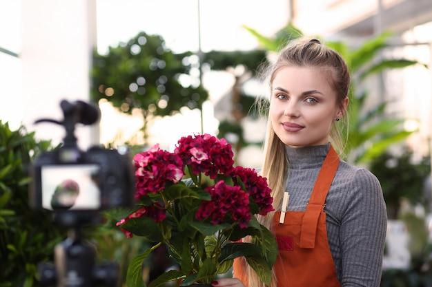 Piękna uśmiechnięta młoda kwiaciarnia w kwiatu sklepie