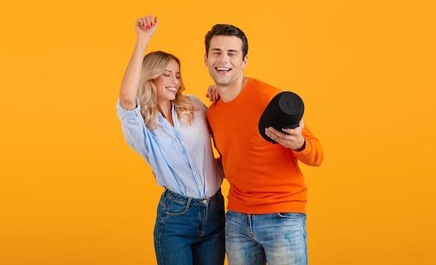 Piękna uśmiechnięta młoda para trzymając bezprzewodowy głośnik, słuchanie muzyki tańczącej na pomarańczowo