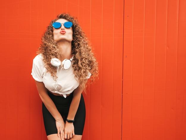 Piękna uśmiechnięta modelka z fryzurą afro loki ubrana w letnie ubrania hipster. seksowna beztroska dziewczyna pozuje w pobliżu czerwonej ściany na zewnątrz. zabawna i pozytywna kobieta bawi się w okularach przeciwsłonecznych. sprawia, że twarz kaczki