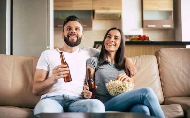 Piękna uśmiechnięta, nowoczesna para zakochanych ogląda jakiś film lub film w telewizji, relaksując się na kanapie we własnym mieszkaniu